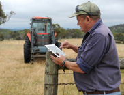 A farmer standing in a field in front of a tractor using an iPad