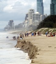 Photo of Australian coastline showing storm damage with people on the beach and buildings in the background