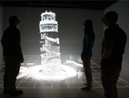 Three people standing around a hologram of the Leaning tower of Pisa