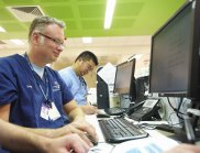 A doctor sitting in front of a computer screen with other medical staff in the background of a hospital room
