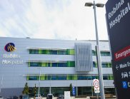 The outside of a three storey building with signage showing Robina Hospital and direction signs