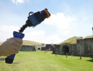 A hand holding the Zebedee, a handheld laser scanner