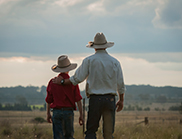 A man and boy wearing hats look out on a paddock.