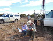 Two scientists taking soil samples in a paddock.
