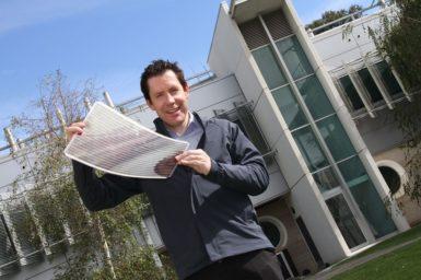 Dr Scott Watkins holding a sheet of flexible solar cells