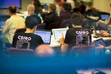 People working at laptops wearing CSIRO tee shirts