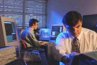 Two men working in a darkened room at computer workstations