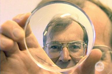 Dr Tony Miller looks through lens.
