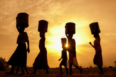 Girls carrying water on their heads.