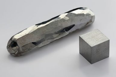 A crystal cadmium bar. Purity 99.999 %. Made by the flux process. As well as a 1 cm3 cadmium cube for comparison.