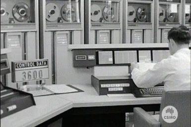 A man setaed at a 1960's computer terminal.
