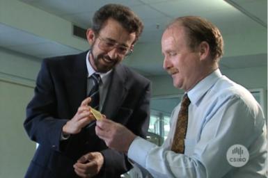 Dr Ezio Rizzardo and fellow researcher examine circuit board.