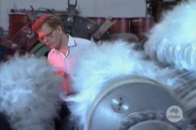 Researcher examining wool carding machine.