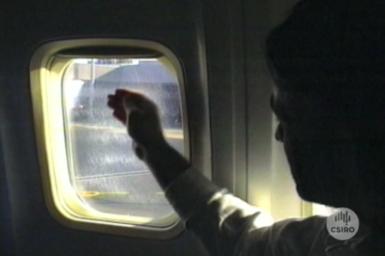 Passenger inspecting aircraft window.