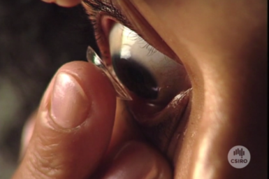 Close up view of woman inserting contact lens.