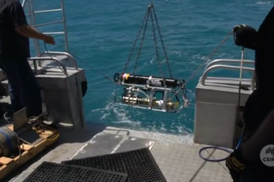 Water monitoring equipment being lowered over the side of research boat.