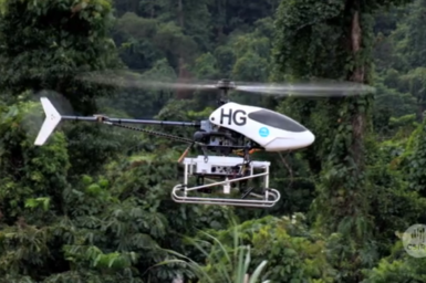 Autonomous helicopter hovering over rainforest.