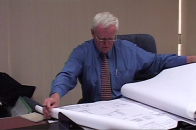 George Harley seated at desk with building plans
