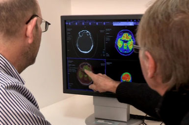 Researchers examining brain scans on computer screen.