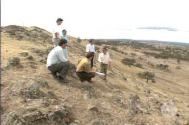 Researchers and planners inspect degraded landscape