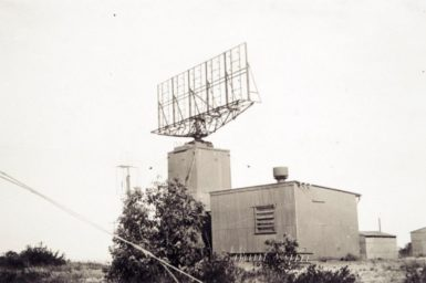 Black and white image of a building with a large antenna on the roof